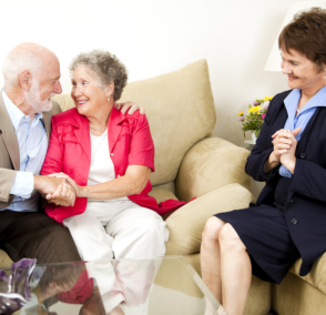 old couple smiling to each other with caregiver happy for them