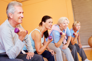 caregiver assisting elderly patients on exercising